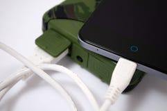 在军事力量银行组装帮助下充电您的电话 免版税库存照片