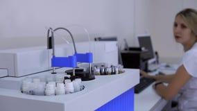 在军医实验室和妇女工作的自动生物化学的分析仪机器在计算机上 影视素材