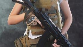 在军用成套装备的年轻白肤金发的女性snipper有攻击步枪的在演播室 股票录像