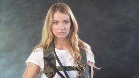 在军用成套装备的年轻白肤金发的女性snipper有攻击步枪的在演播室 影视素材