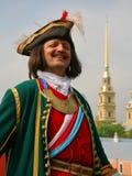 在军用服装的Reconstructor从在背景的18世纪彼得和保罗大教堂的尖顶 库存照片