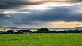 在农场和距离小山的云彩形成 免版税库存照片
