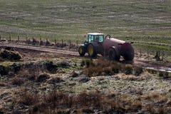 在农场径赛服的拖拉机和肥料坦克 免版税库存图片