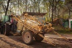 在农场的拖车肥料喷雾器在房子附近 免版税库存照片