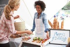 在农夫新鲜的食品批发市场的女性面包店摊位持有人 图库摄影