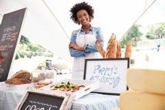 在农夫新鲜的食品批发市场的女性面包店摊位持有人 免版税库存照片