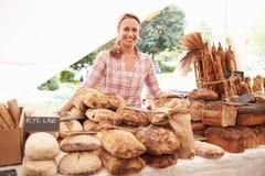 在农夫新鲜的食品批发市场的女性面包店摊位持有人 免版税图库摄影