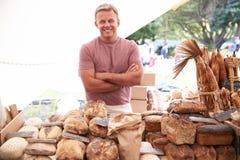 在农夫新鲜的食品批发市场的男性面包店摊位持有人 免版税库存图片