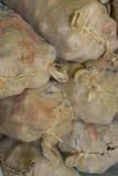 在农夫的市场上堆积的大粗麻布袋红色土豆待售。垂直。能是棕色,织地不很细,土气背景 免版税库存图片