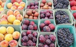 在农夫` s市场摊位包括,成熟桃子、紫色李子和葡萄的被分类的果子 免版税库存图片