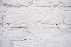 在农村屋子里提取浅灰色被风化的纹理被弄脏的老的灰泥并且绘白色砖墙背景,脏 库存图片