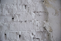 在农村屋子里提取浅灰色被风化的纹理被弄脏的老的灰泥并且绘白色砖墙背景,脏 免版税库存图片