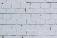 在农村屋子,脏的生锈的bl里提取浅灰色被风化的纹理被弄脏的老的灰泥并且变老了油漆白色砖墙背景 免版税库存照片