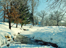 在农村房子晴朗的天气冬天视图的冬天风景有小河和冬天随风飘飞的雪的在前景 库存照片