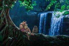 在农村的Hildren在树下坐在瀑布的岩石 库存照片