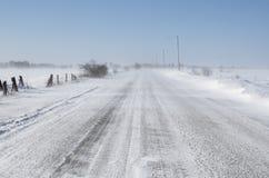 在农村路的低吹雪 免版税库存图片