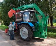 在农村路的司机拖拉机 库存图片