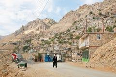 在农村路的库尔德人步行从老mountaine村庄在中东 免版税库存图片