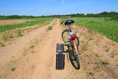 在农村路的老自行车 免版税库存照片