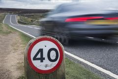 在农村路的限速标志有汽车的 免版税图库摄影