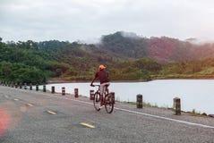 在农村路神色的愉快的亚洲人骑马自行车对准备好的自然起动假期去冒险旅行,探索,发现世界 免版税库存照片