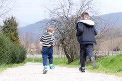 在农村路跑的两个男孩 库存图片
