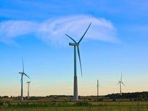 在农村领域的风车在日落 可选择能源农厂来源涡轮风 免版税图库摄影
