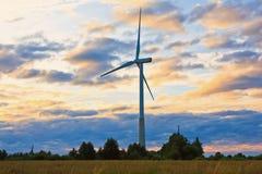在农村领域的风车在日落 可选择能源农厂来源涡轮风 免版税库存照片
