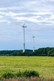 在农村领域的风车在日落 可选择能源农厂来源涡轮风 免版税库存图片