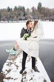 在冬天亲吻新娘和新郎在步行 免版税库存照片