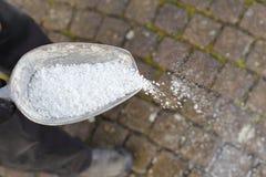 在冬天供以人员在一条道路的传播的除冰的盐 免版税库存图片