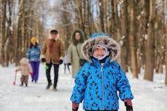 在冬天公园哄骗赛跑并且获得与家庭的乐趣 免版税图库摄影