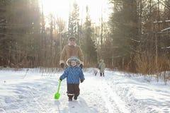 在冬天公园哄骗赛跑并且获得与家庭的乐趣 图库摄影