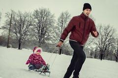 在冬天公园生雪撬的辗压女儿 免版税库存图片