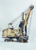 在冬天关闭的老黄色挖掘机 免版税库存图片