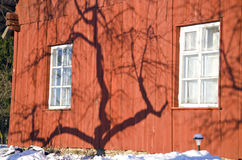 在冬天农厂房子墙壁上的苹果树阴影 免版税图库摄影