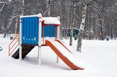 在冬天前面的孩子的幻灯片 免版税库存图片