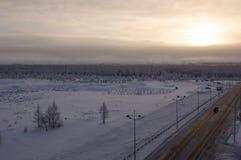 在冬天北部街道的路 夜间,日落 免版税库存照片