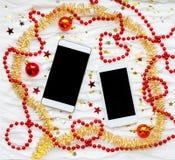 在冬天圣诞节假日背景的两个智能手机 图库摄影