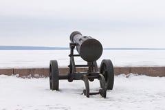 在冬天堤防的老生铁大炮 免版税图库摄影