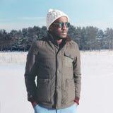 在冬天塑造时髦年轻非洲人佩带太阳镜和夹克有被编织的帽子的 免版税库存图片