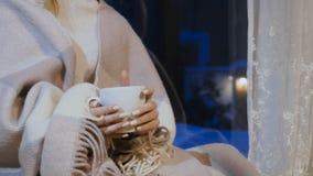 在冬天夜期间,在格子花呢披肩下的女孩有茶的坐窗口基石 股票录像