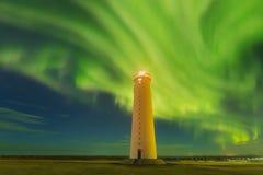 在冬天夜期间,这美丽的北极光或极光borealis在冰岛被采取了在或在凯夫拉维克附近的灯塔附近 库存图片