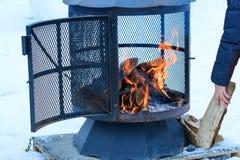 在冬天季节的壁炉充电与木柴,在灼烧的过程中 免版税库存图片