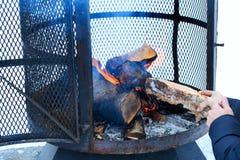 在冬天季节的室外金属壁炉充电与木柴,在灼烧的过程中 库存照片