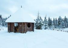 在冬天小山上面的木summerhouse。 免版税图库摄影