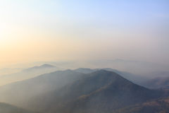 在冬天山的日出,有薄雾的梦想的风景 库存照片