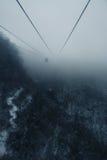 在冬天山的浓雾风景缆车鸟瞰图 库存照片