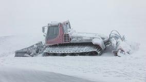 在冬天山的红色ratrak snowcat 用雪报道的一红色雪tucker 免版税库存照片