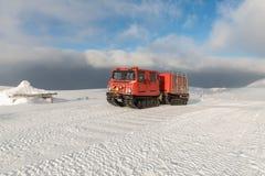 在冬天山的红色ratrak snowcat 用雪报道的一红色雪tucker 库存图片